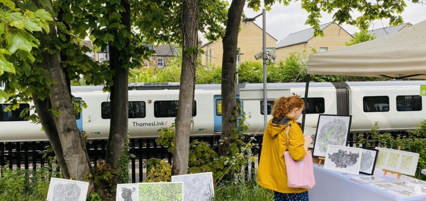 A woman in a yellow jacket peruses the Me on the Map stall. A Thameslink train is stopped at the platform in the background.